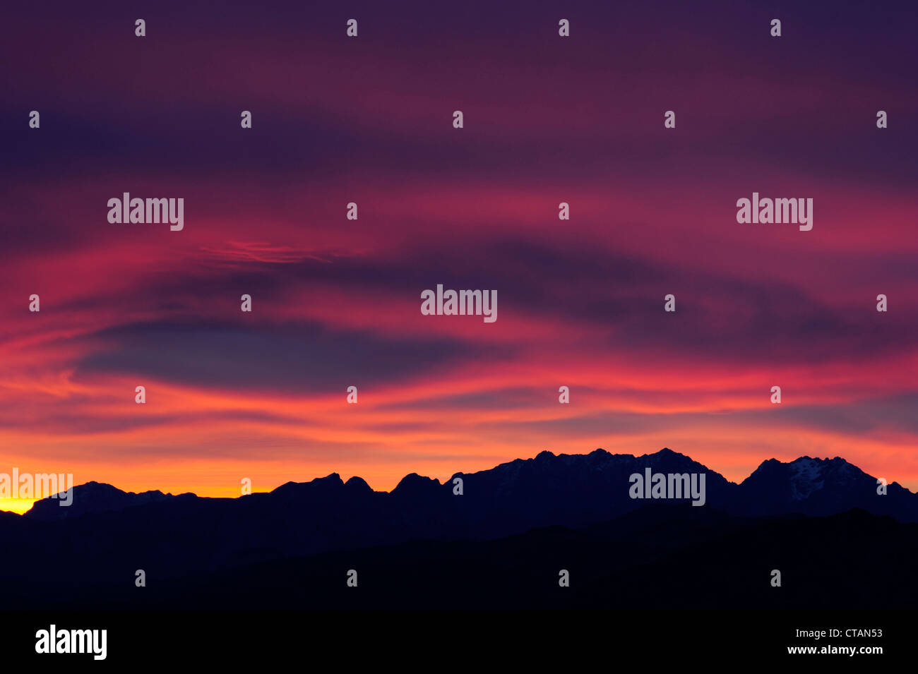 Clouds above silhouettes of Berchtesgaden range with Hoher Goell, Watzmann, Hochkalter and Hocheiser in the afterglow, Stock Photo
