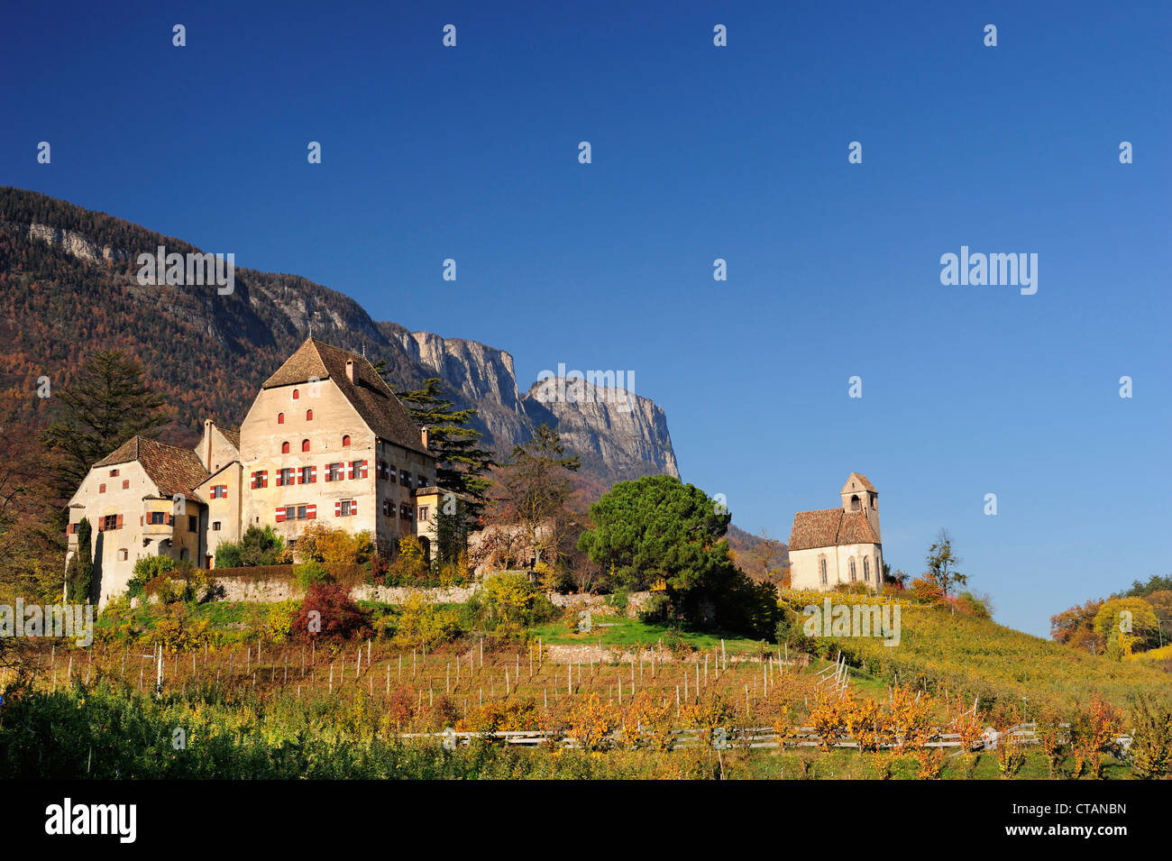 Manor house and church in vineyards in autumn colours with rockface in background, near lake Kalterer See, South - Stock Image