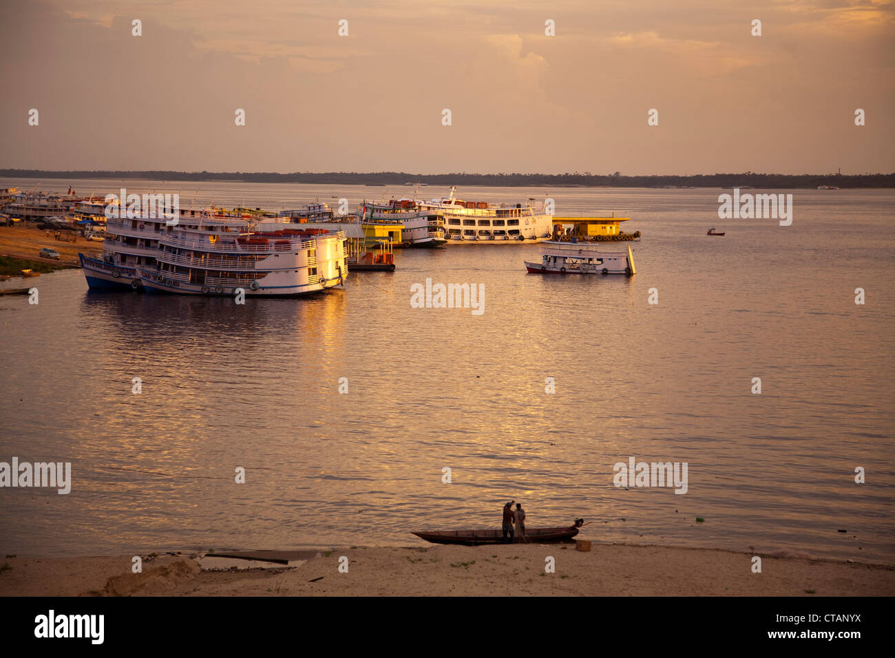 Fishermen in canoe and Amazon river boats at sunset, Manaus, Amazonas, Brazil, South America - Stock Image