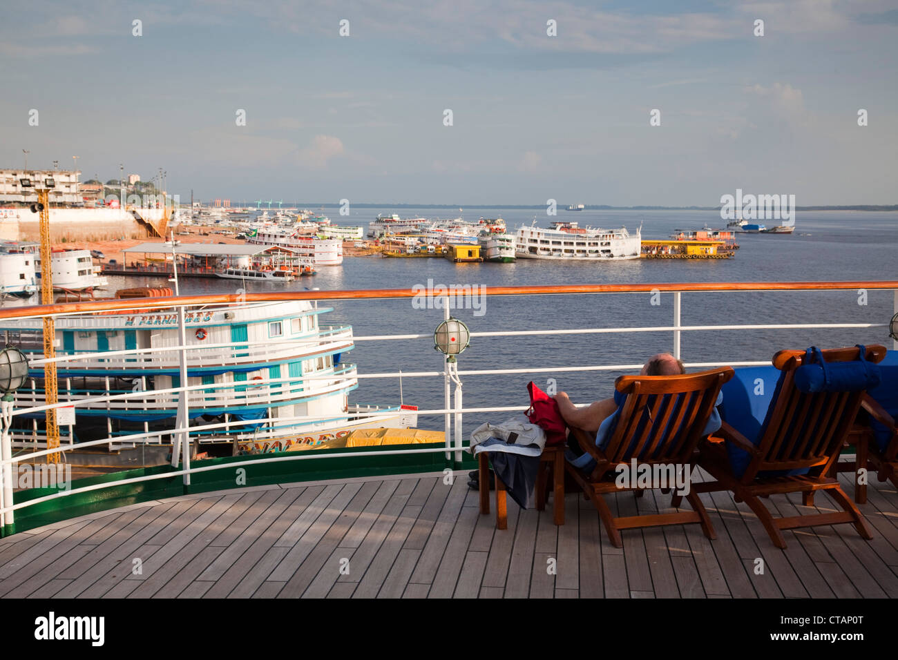 Guest on deck of cruise ship MS Deutschland, Reederei Peter Deilmann, with view of Amazon river boats, Manaus, Amazonas, - Stock Image