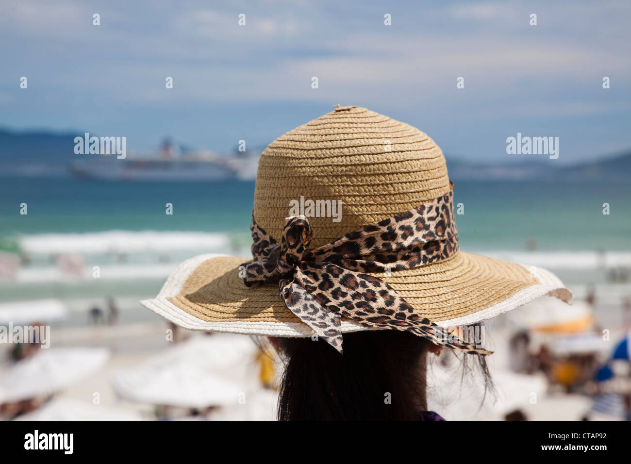 Woman with sun hat on Praia do Forte beach, Cabo Frio, Rio de Janeiro, Brazil, South America - Stock Image