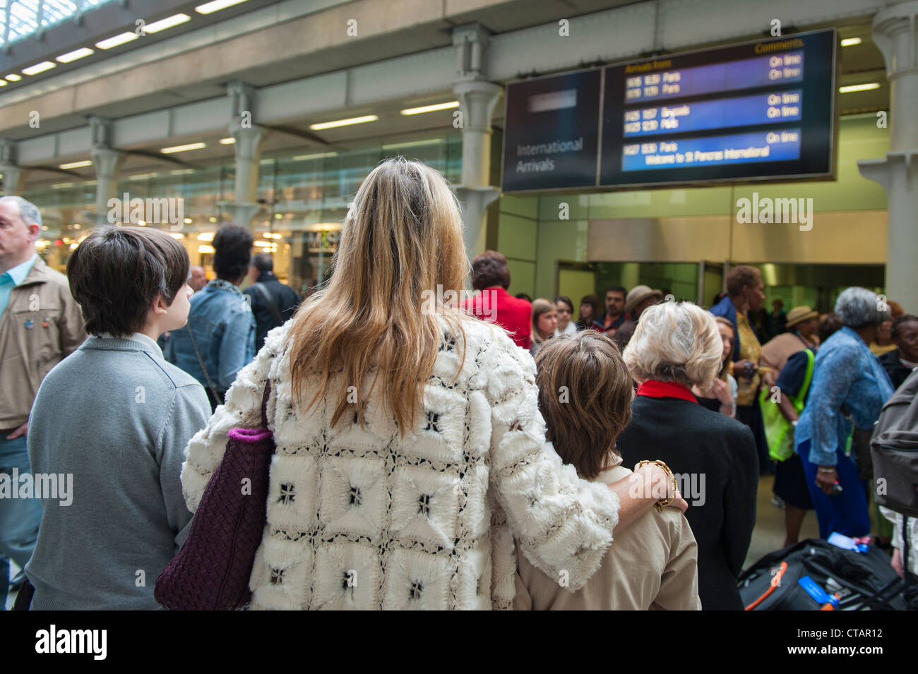 London , St Pancras Station , back rear view of family mother boys waiting at gate by train arrivals information - Stock Image