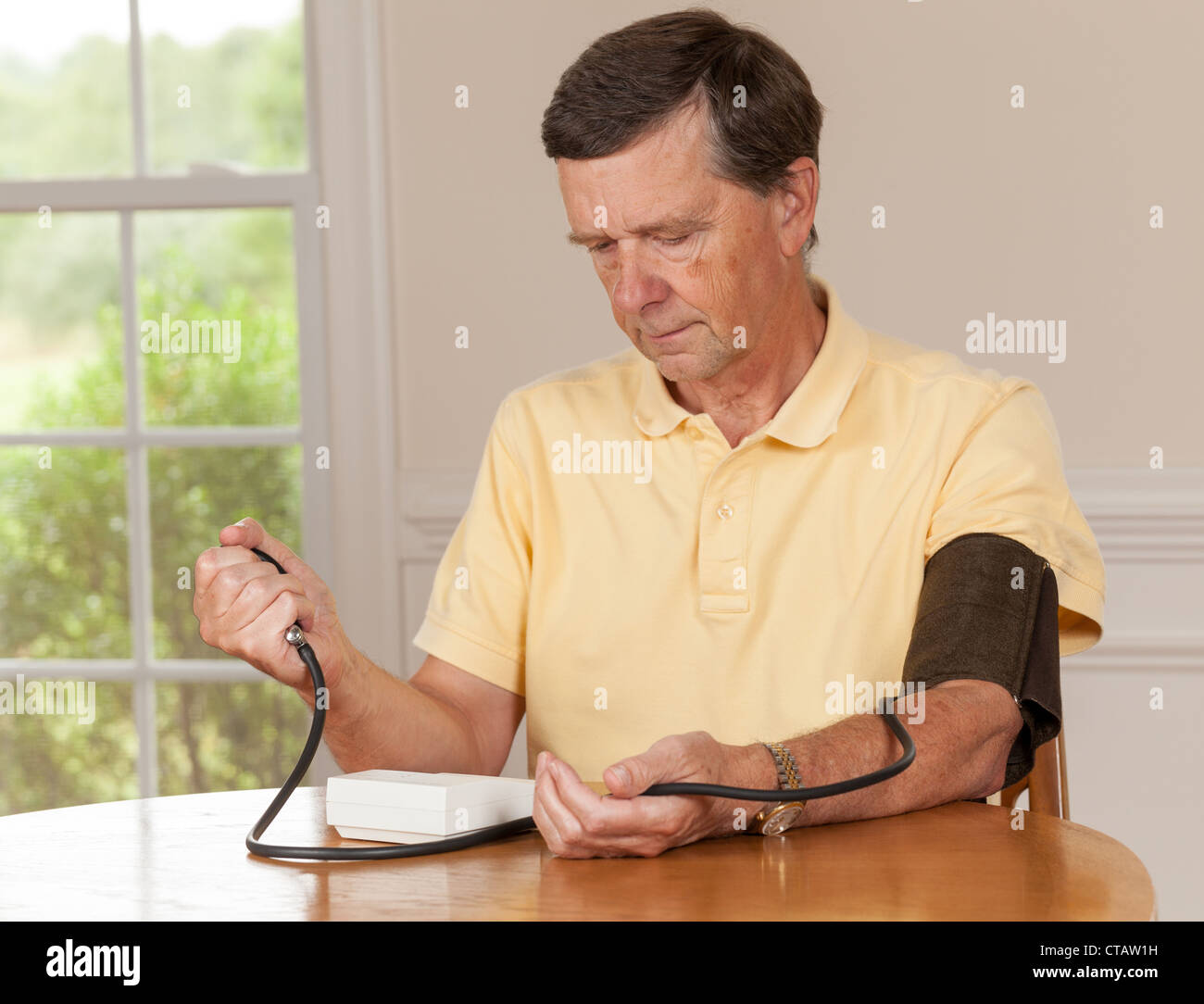 Senior caucasian retired male taking blood pressure at home - Stock Image