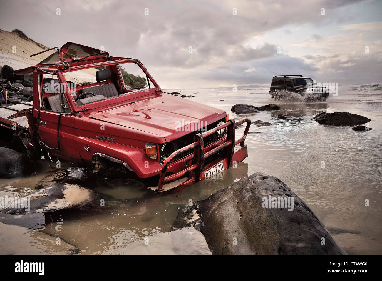 Stranded offroad vehicle at Rainbow Beach, water crossing at high tide, Queensland, Australia - Stock Image