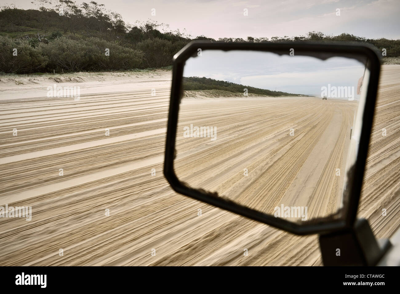 Offroad vehicle in mirror while driving at sand island, Fraser Island, UNESCO world herritage, Queensland, Australia - Stock Image