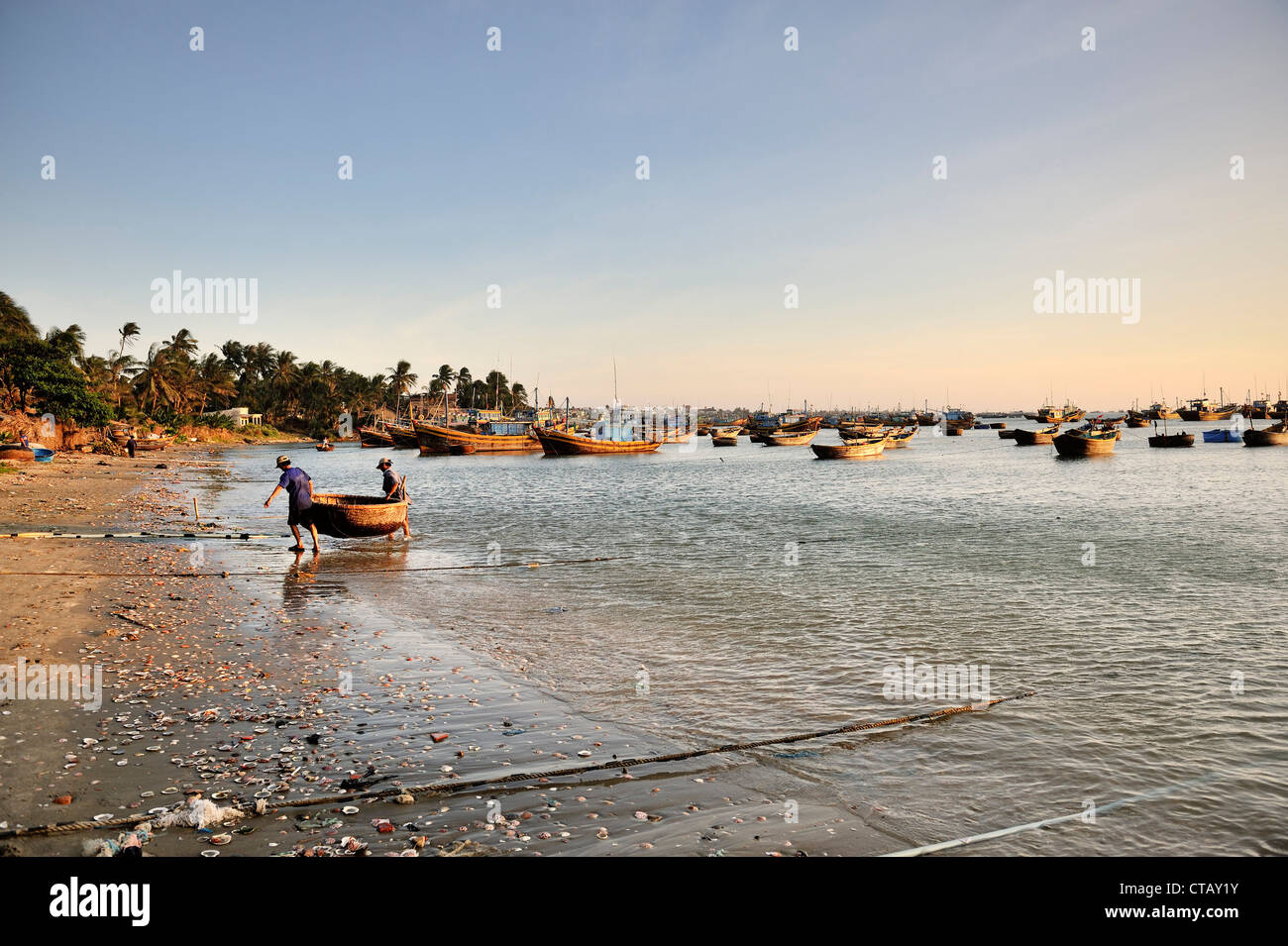 Fishers carry their small boat to the beach, fishing boats, fishing village, South China Sea, Mui Ne, Binh Thuan, - Stock Image