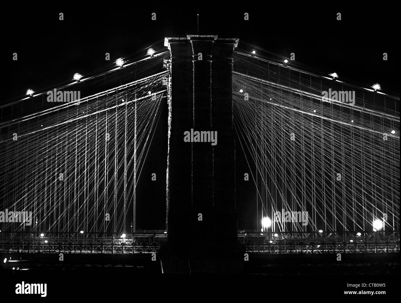 Side night view of the Brooklyn Bridge, New York City. Note fan-like spread of cables in this famous suspension - Stock Image