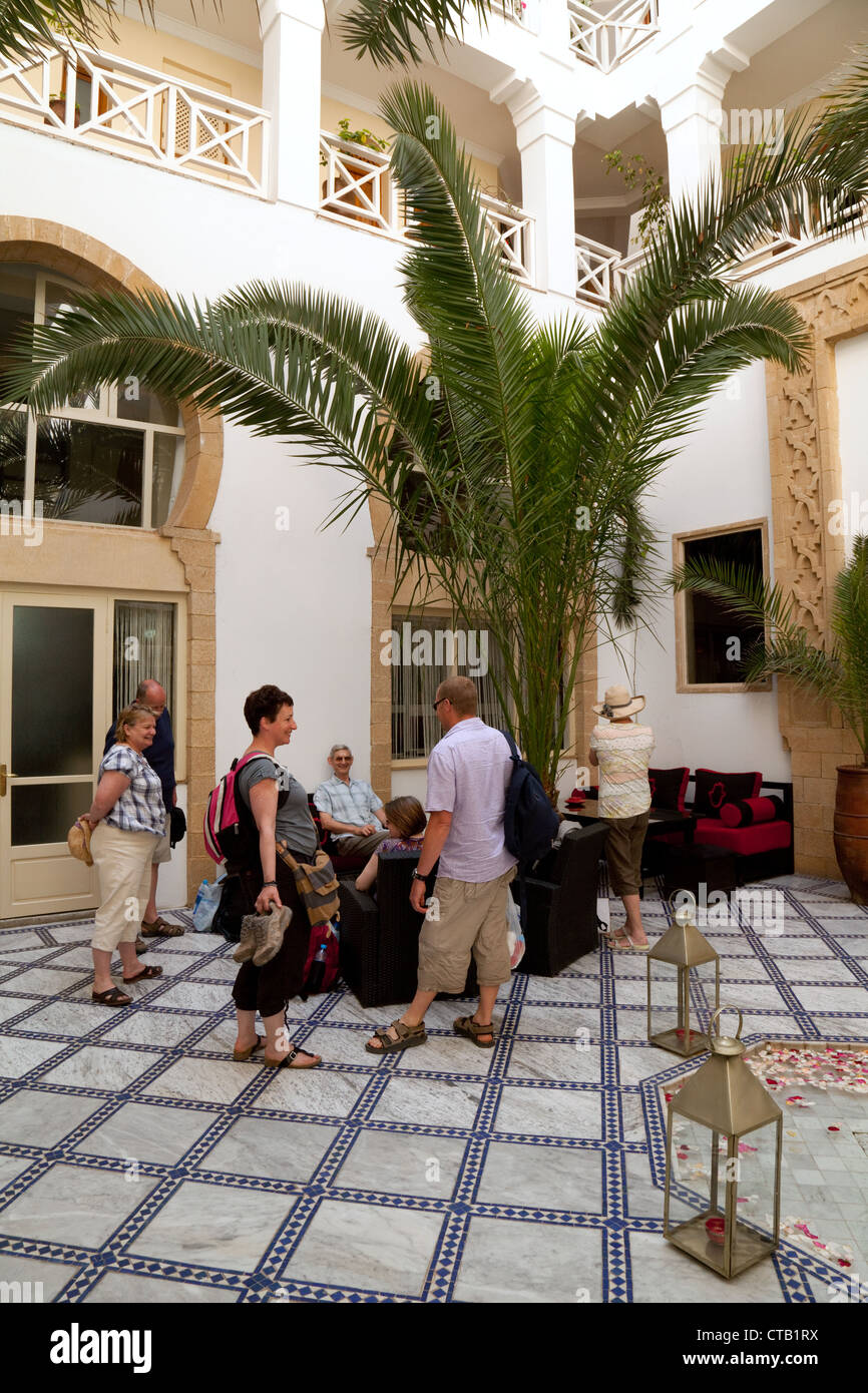 Guests arriving in the reception area of the Riad Dar L'Ouissa Hotel, Essaouira, Morocco Africa - Stock Image