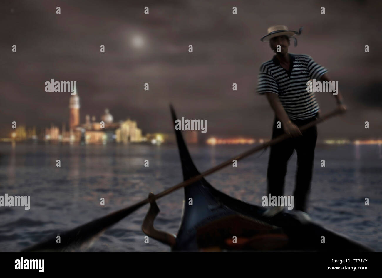 Gondolier wtih gondola at night with a city view in the background, Venice, Italien - Stock Image