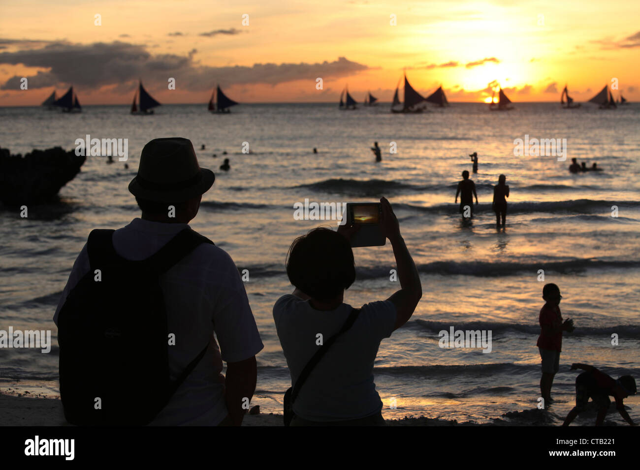 Two tourists making pictures at sunset, Boracay, Panay Island, Visayas, Philippines - Stock Image