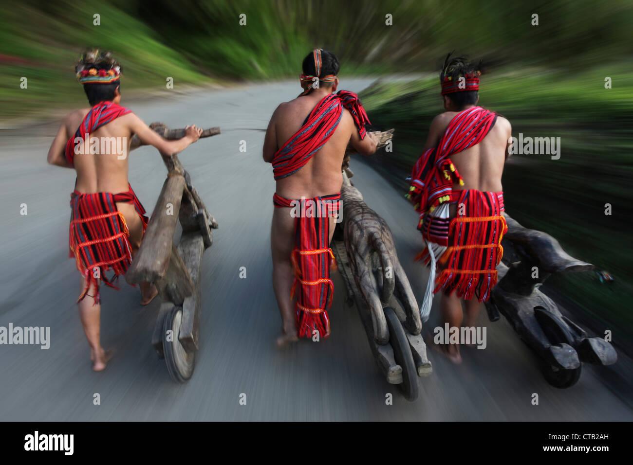 Ifugao men speeding on wooden scooters, Banaue, Ifugao, Luzon Island, Philippines - Stock Image