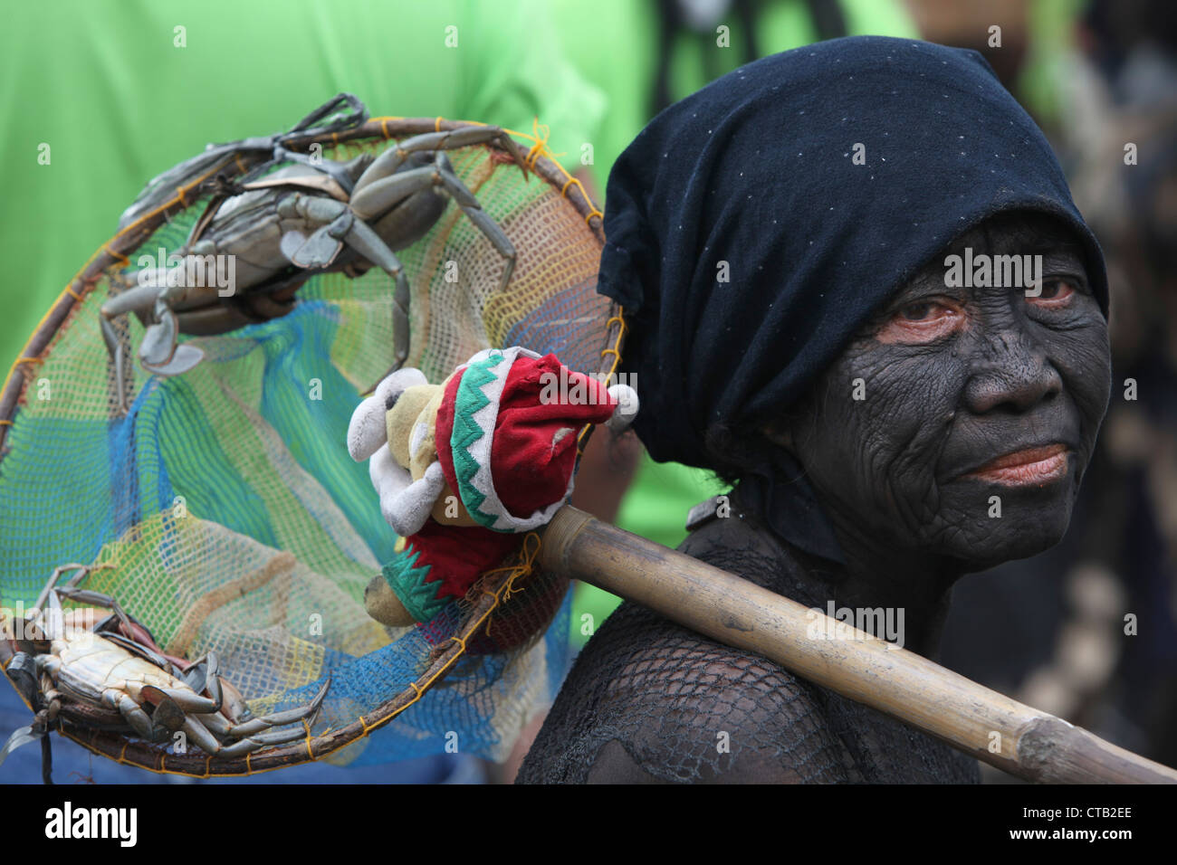Woman with facial painting holding offerings at Ati Atihan festival, Ibajay, Aklan, Panay Island, Visayas, Philippines - Stock Image