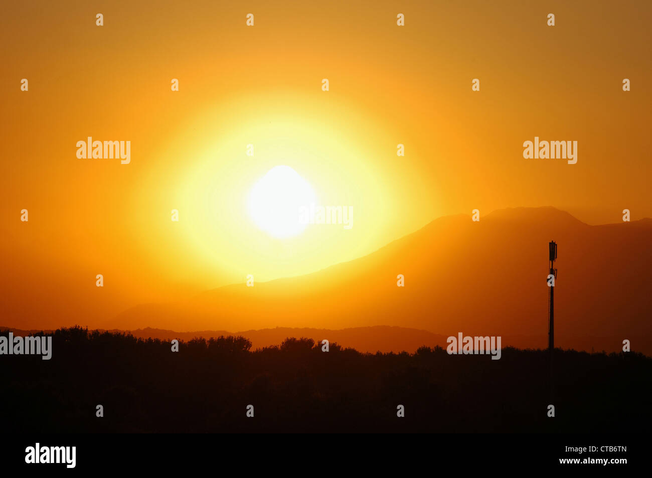 A telcom tower stands against the red sunset sky - Stock Image