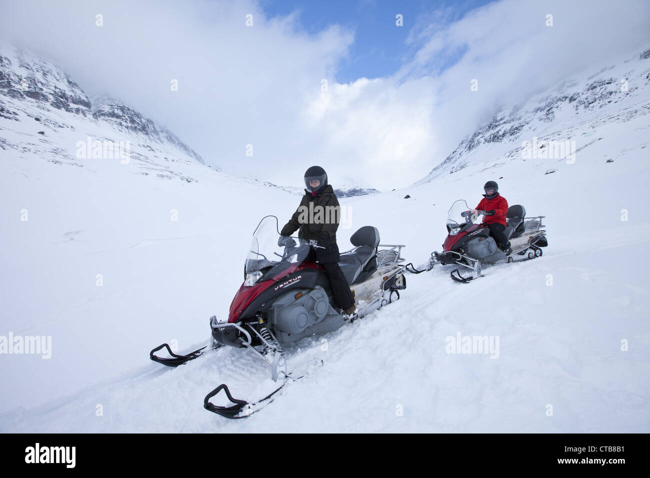 Snowmobiling in the arctic alps in the Arctic Circle near Holt in the region of Tromso, Northern Norway - Stock Image
