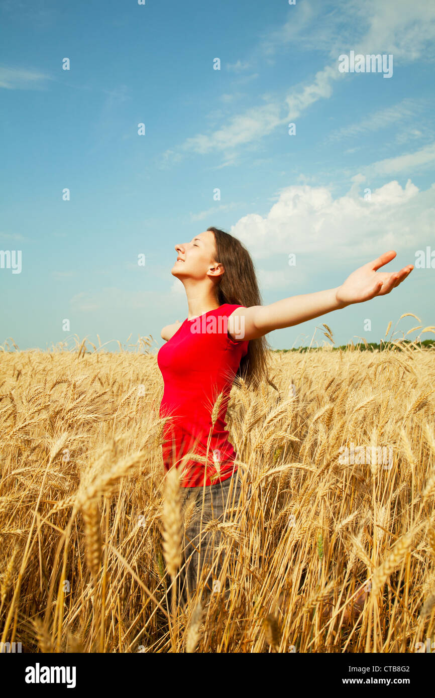 Teen girl staying at a wheat field with her arms outstretched - Stock Image