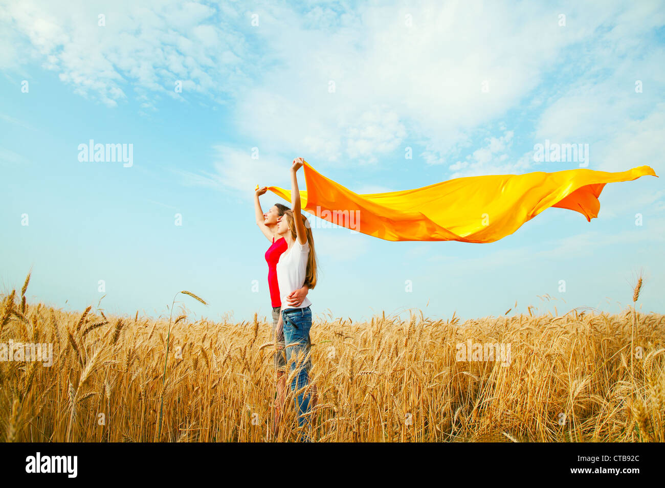 Teen girls at a wheat field with yellow fabric - Stock Image