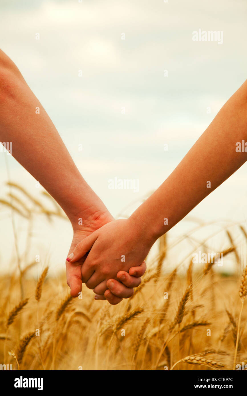Young couple holding hands in the evening time - Stock Image