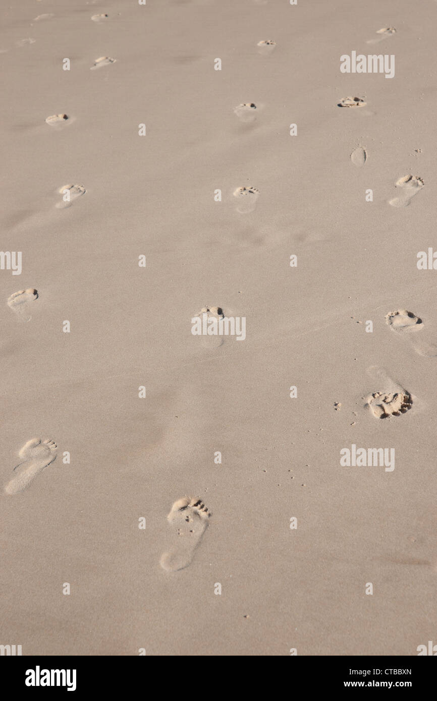 indecision with footprints in sand going back and forth - Stock Image