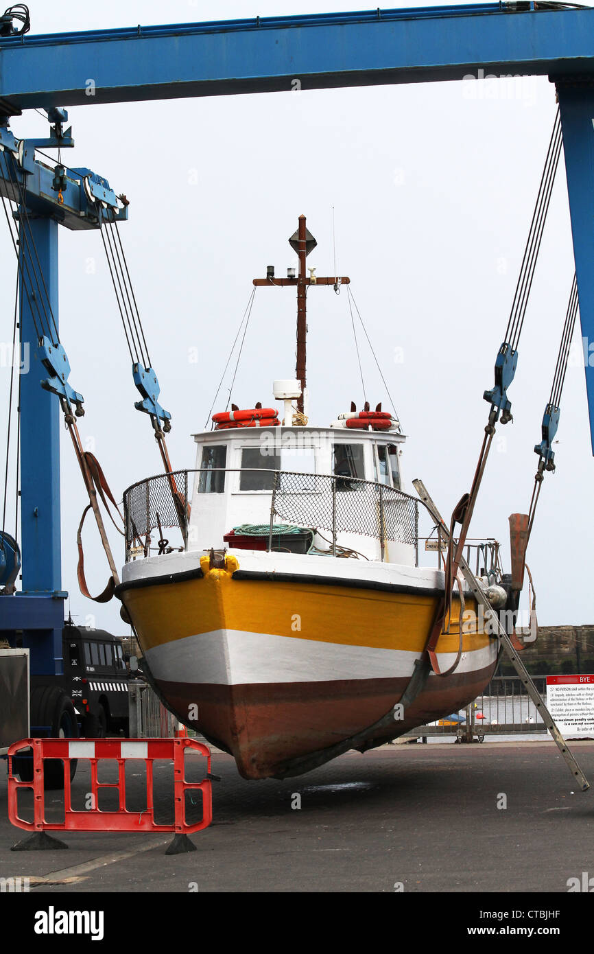 Boat in crane lift sling on harbor quay side for repair work Stock