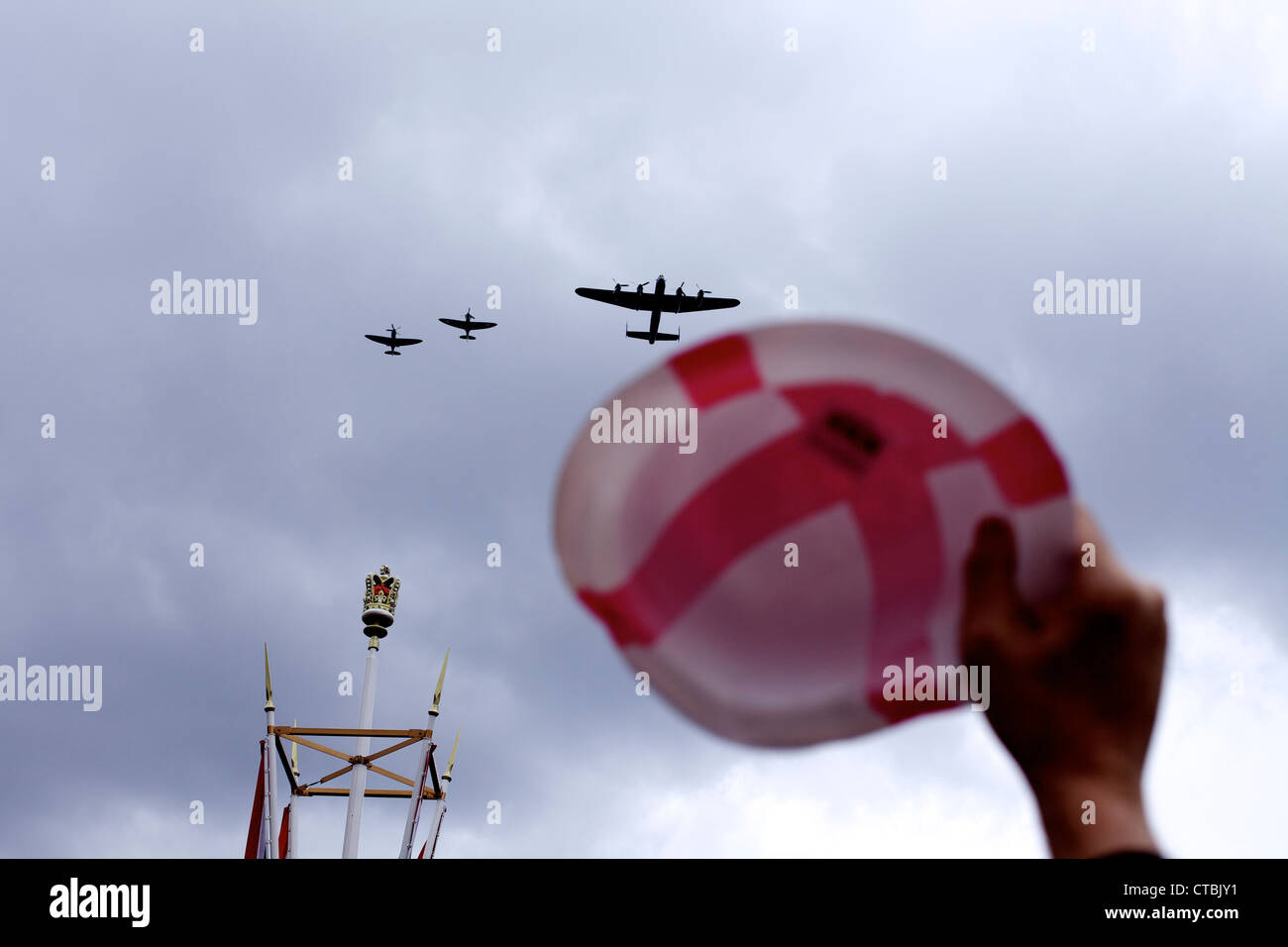 A Lancaster bomber and two Spitfires fly past against a foreground of crown a hat featuring a Saint George's - Stock Image