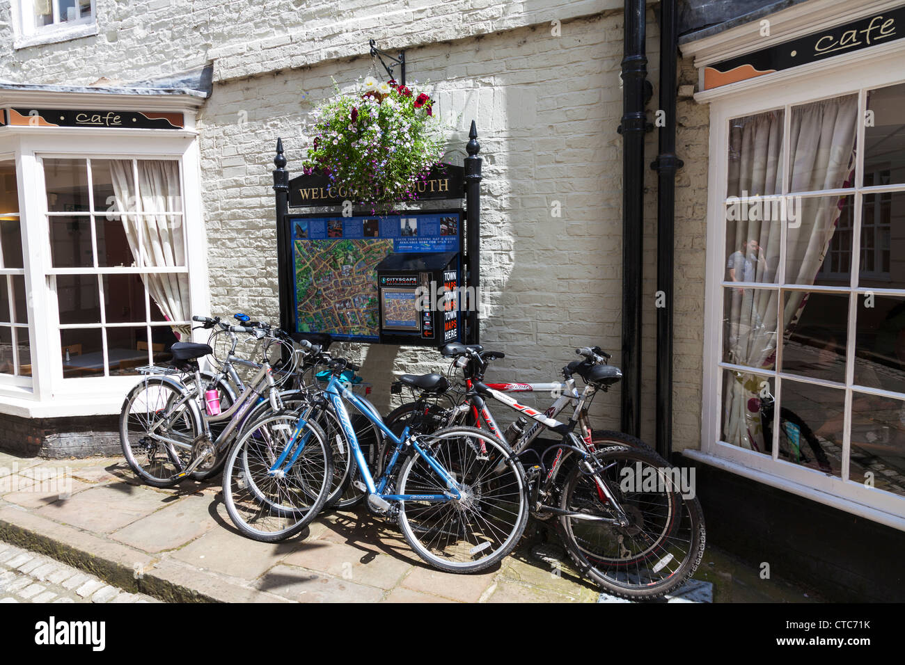 A pile of bikes pushbikes leant against wall and sign outside Cafe in Louth, Lincolnshire - Stock Image