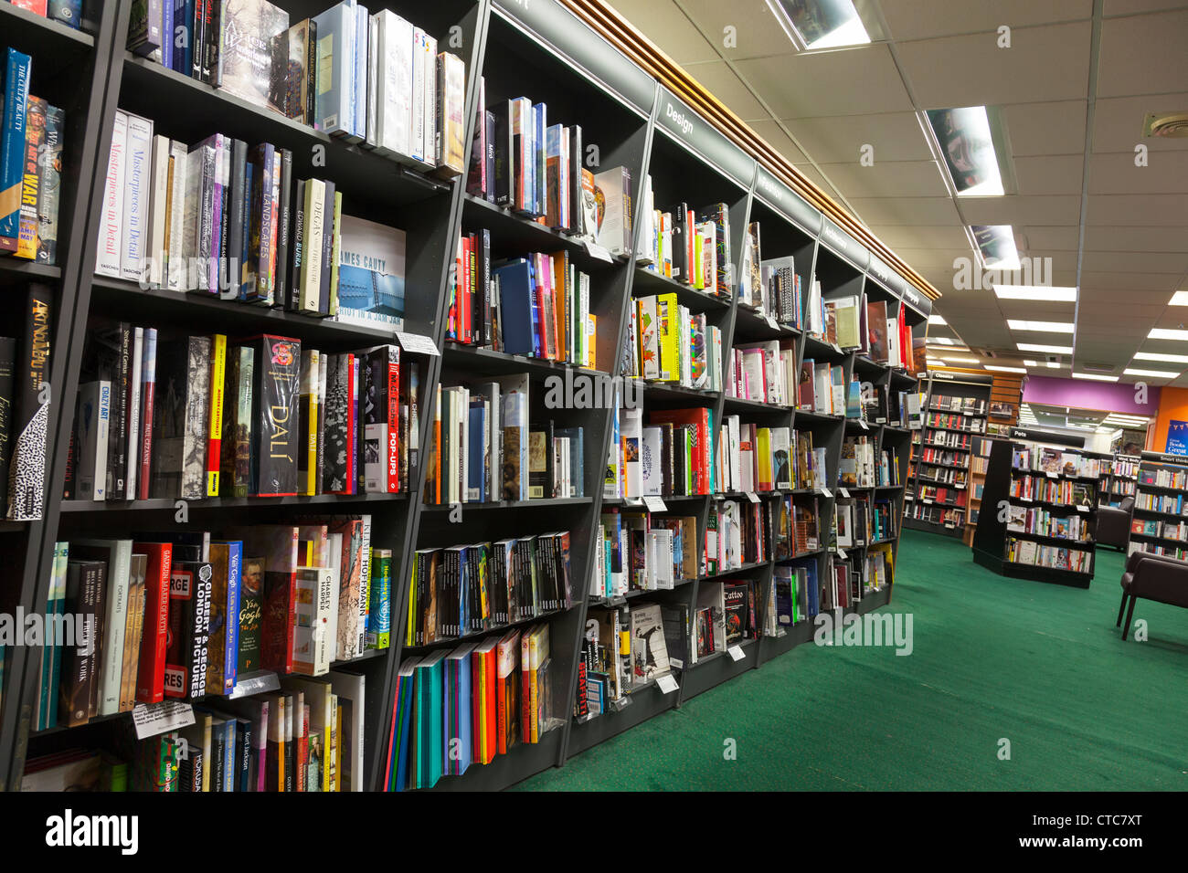 Book shelves inside a Waterstones bookstore shop books lined up and green carpet - Stock Image