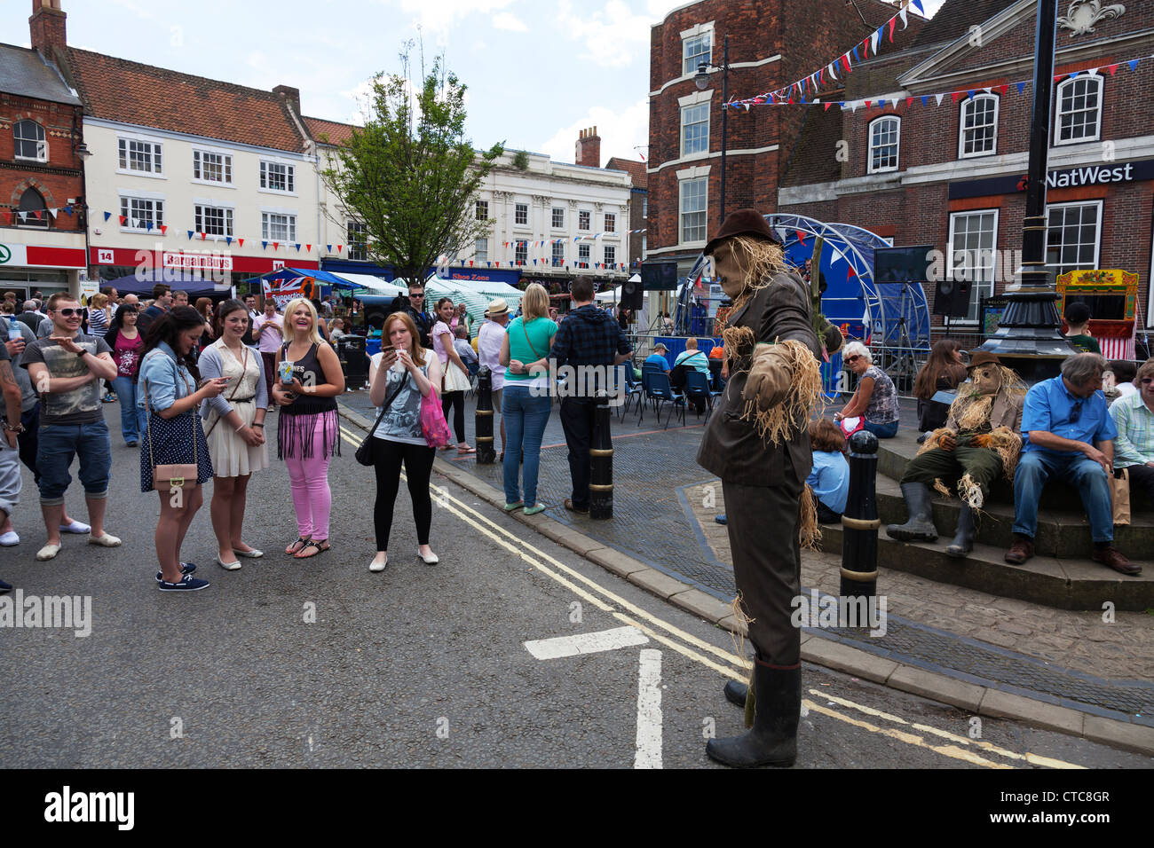 Market stalls and man dressed as scarecrow  at Louth food festival Lincolnshire, UK, England - Stock Image