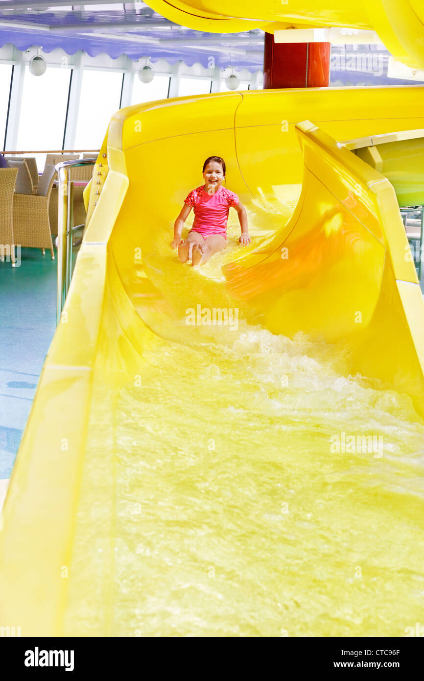 Young girl having fun nearing the end of the water slide - Stock Image
