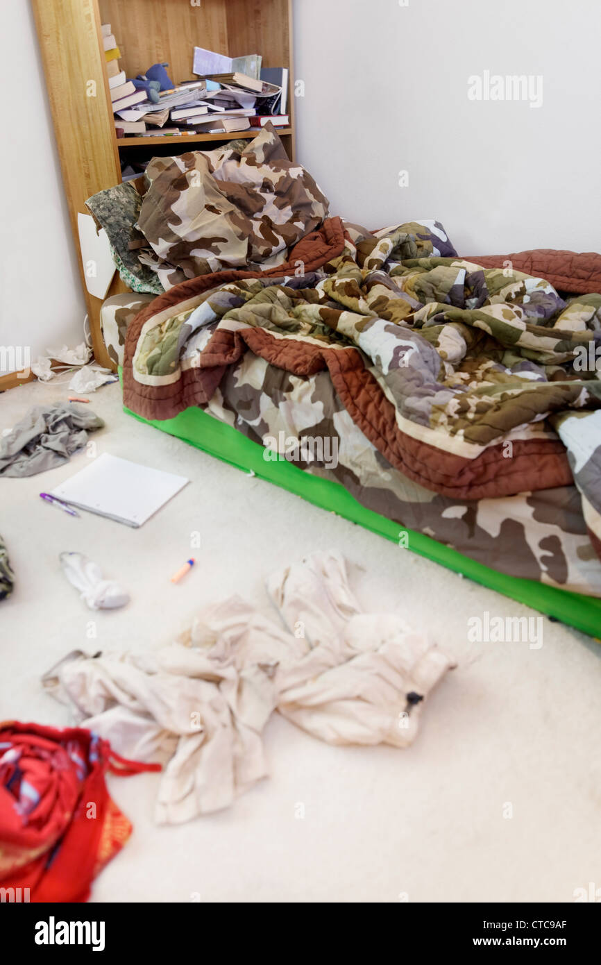 Teenage boy's messy room. Tilt shift lens, with focus on pillow - Stock Image