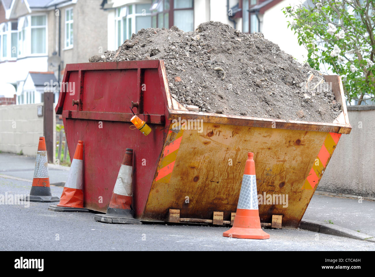 Skip, rubbish skip on residential street, Britain, UK - Stock Image