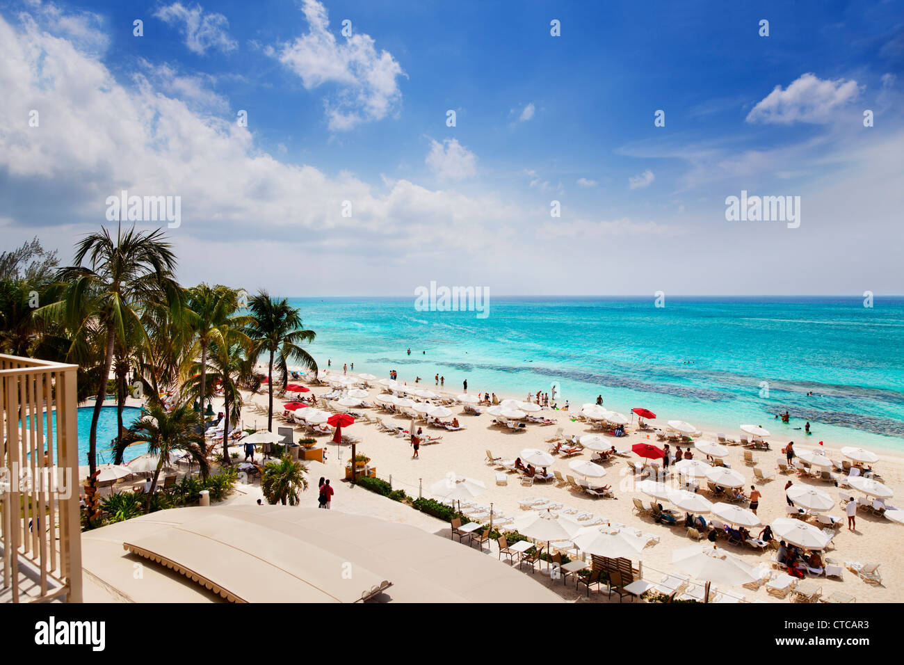 Vacationers enjoying the sun on Grand Cayman's Seven Mile Beach - Stock Image