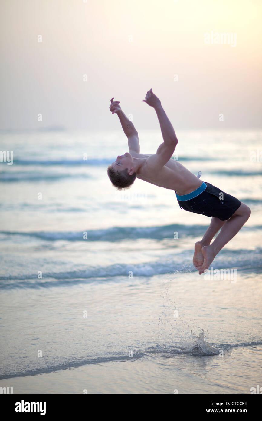 16 year old boy doing back flip on beach. - Stock Image