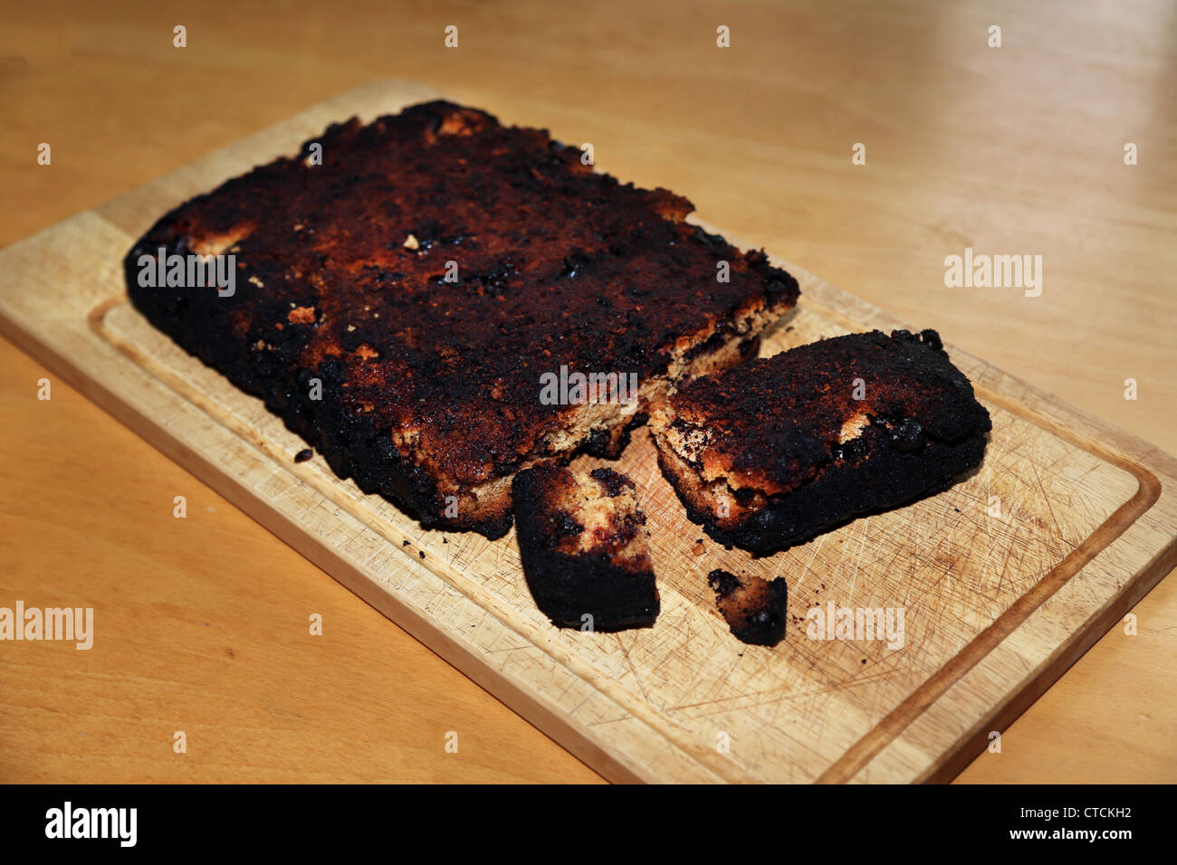 Burnt Cake With A Piece Cut Off On Chopping Board - Stock Image