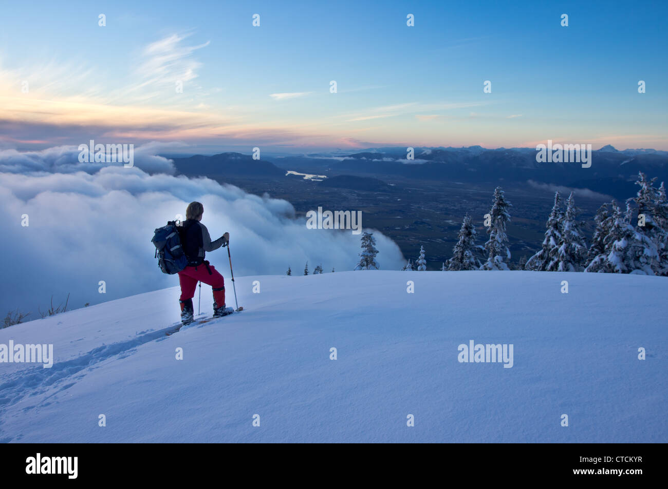 A male snowshoer pauses at a viewpoint to view the scenery below. - Stock Image