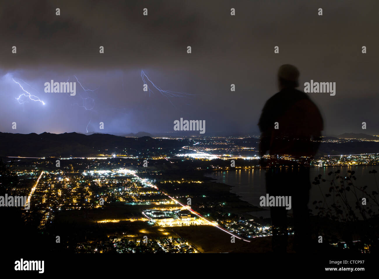 Silhouette of a young man watching a lighting storm over lake elsinore Stock Photo