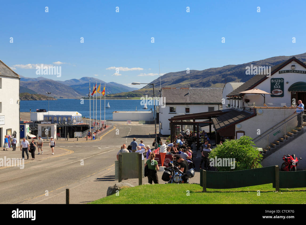 Bar and restaurant with people sitting outside in west highlands coast town on Loch Broom in summer. Ullapool Scotland - Stock Image