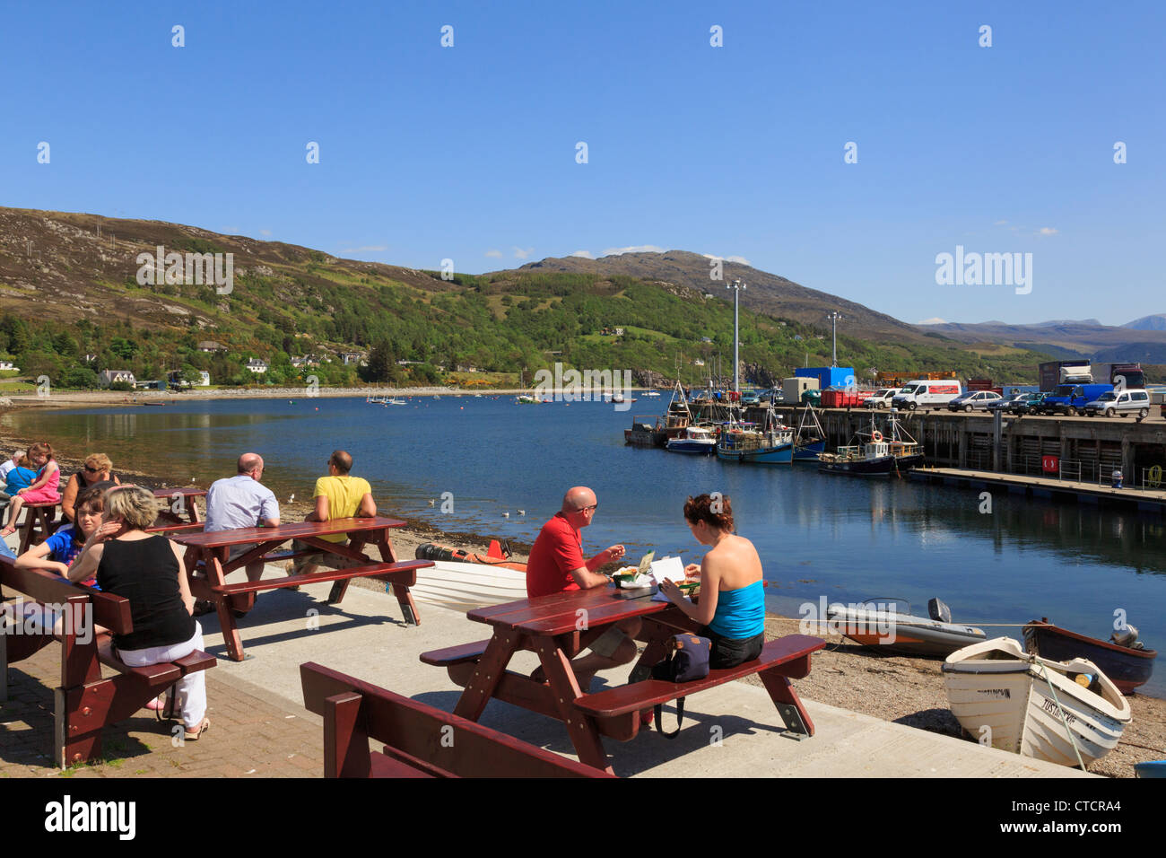 People sitting at picnic tables on seafront with Loch Broom fishing harbour on northwest highlands coast in summer - Stock Image