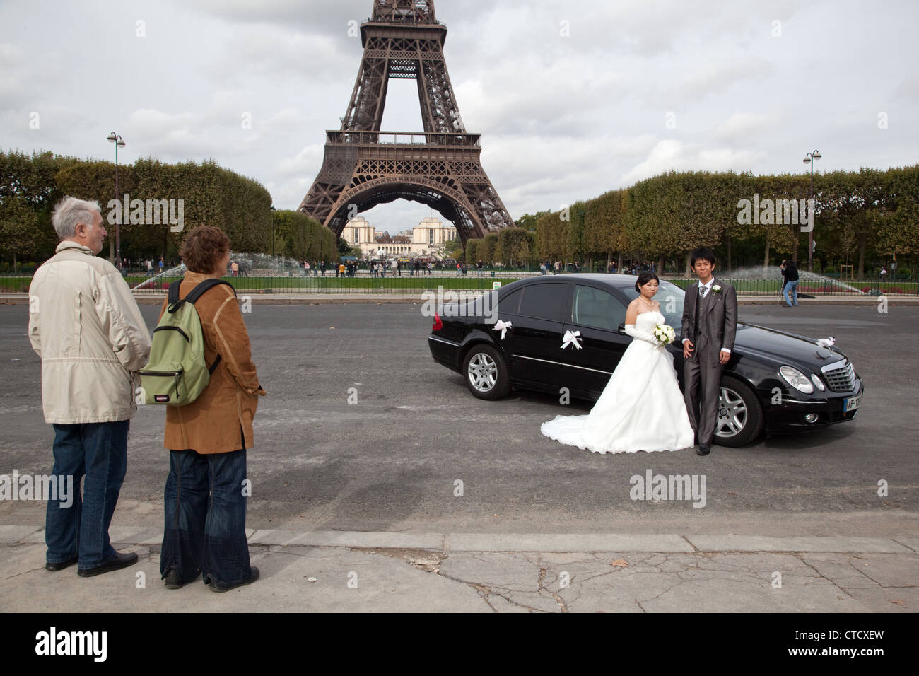 Foreign tourist look at a Chinese couple posing to wedding photos in the Field of Mars near Eiffel Tower in Paris, - Stock Image