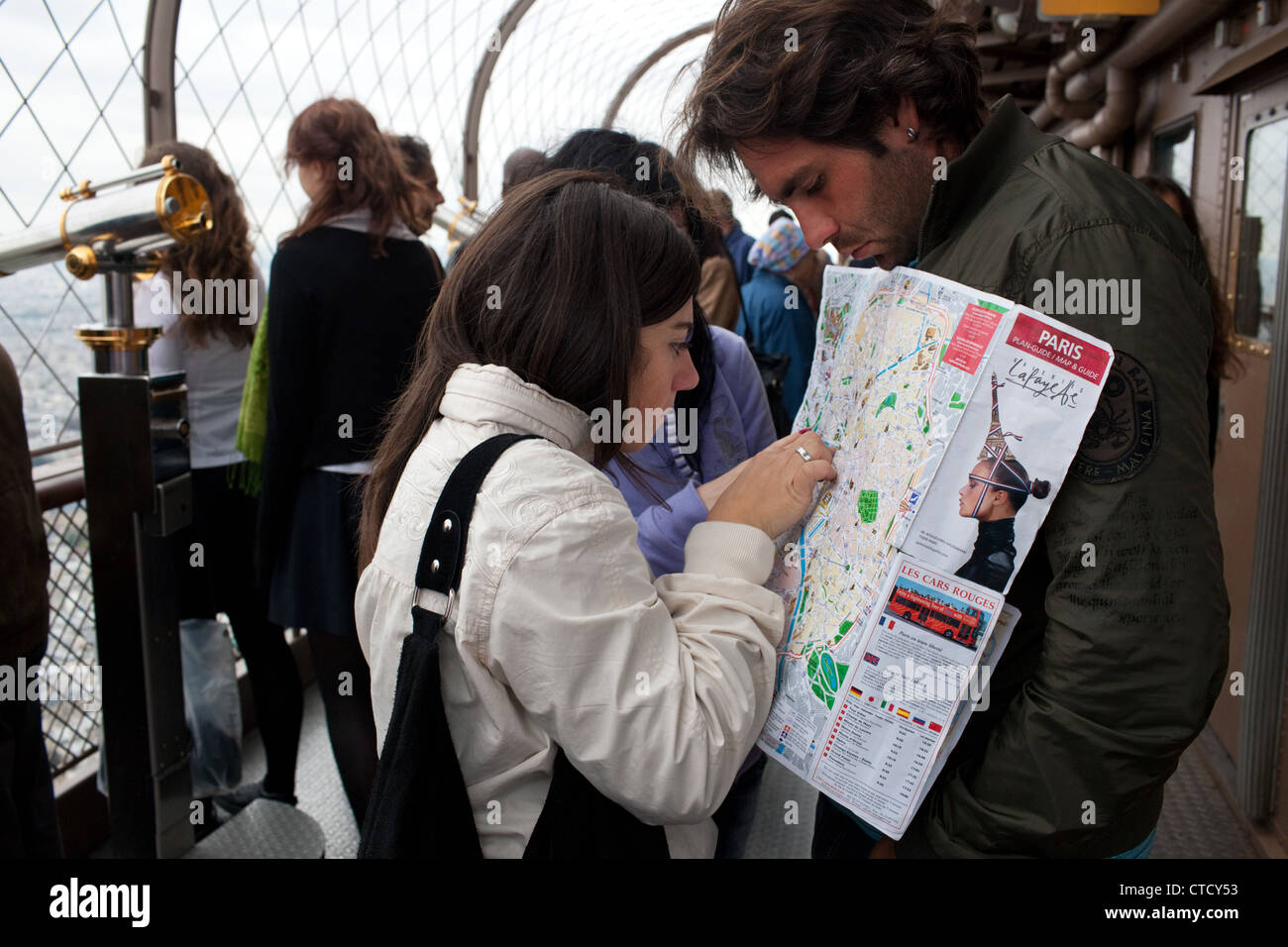 Tourists with a map of Paris on the second floor Eiffel Tower in Paris, France. Stock Photo