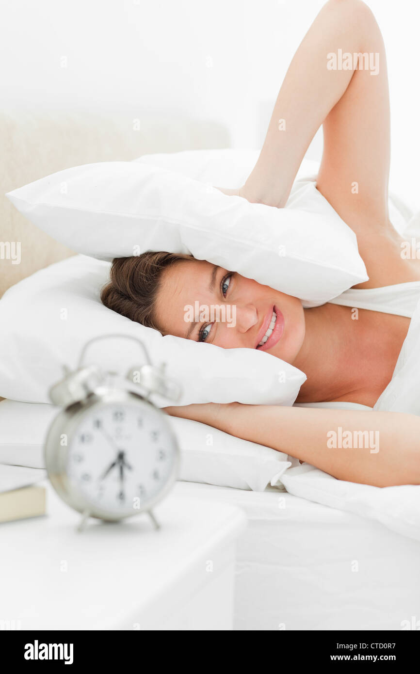 Woman crying while her alarm is ringing loudly - Stock Image