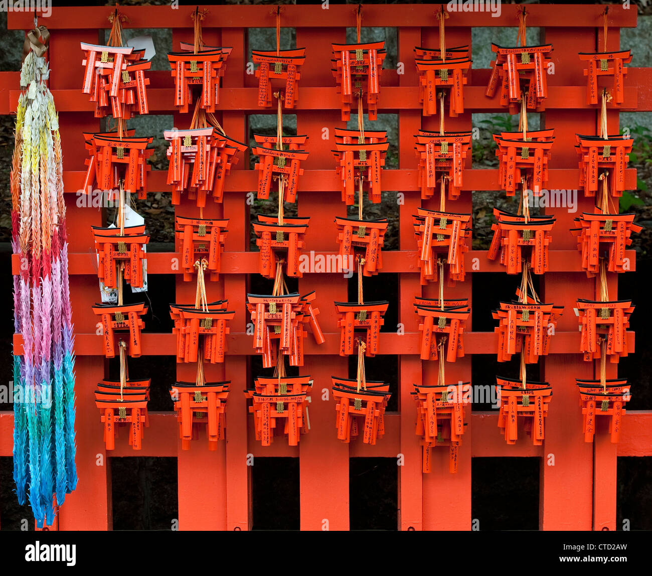 The Shinto shrine of Fushimi Inari-taisha, Kyoto, Japan. Miniature votive torii gates left as offerings by pilgrims - Stock Image