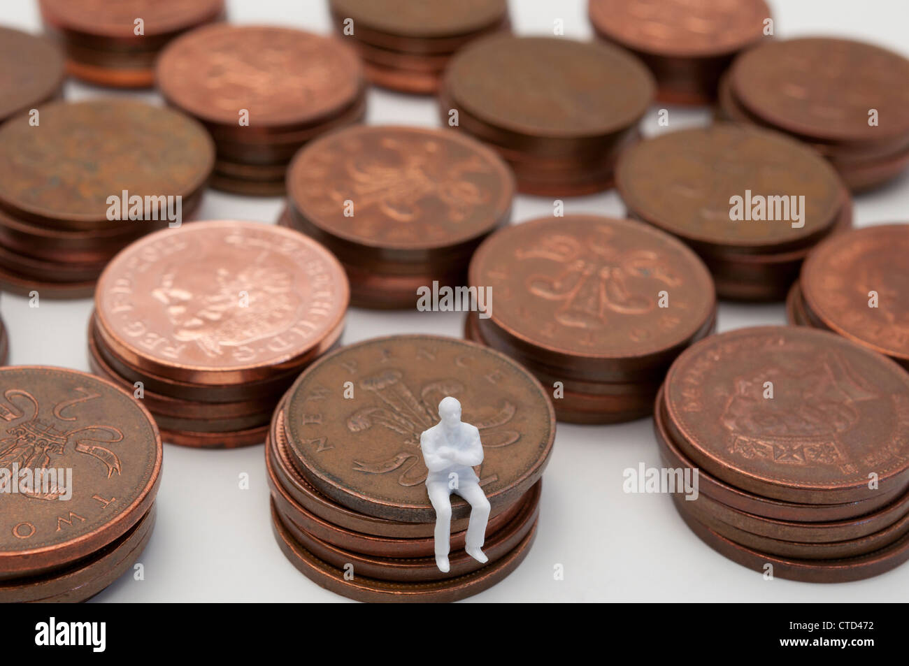 Worried figure sitting on pile of copper two pence pieces - Stock Image