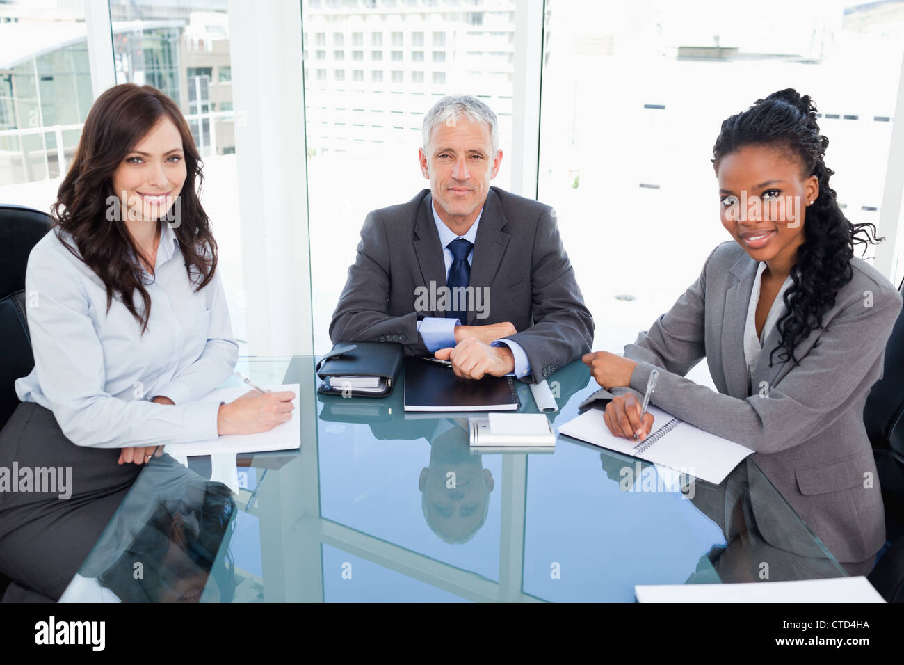 Mature director sitting at the desk and accompanied by two businesswomen - Stock Image