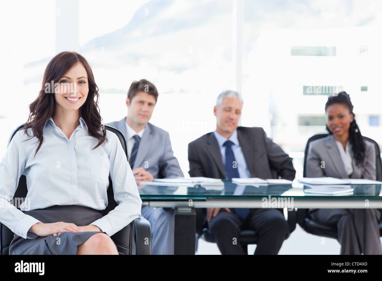 Young businesswoman sitting with her hand on her leg and accompanied by her team - Stock Image