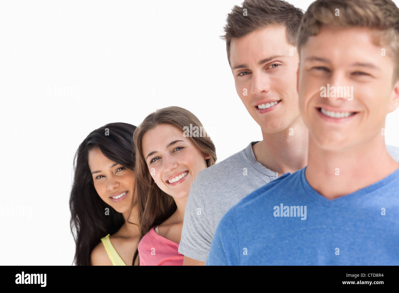 Four people standing in a line with each person angled out a little more - Stock Image