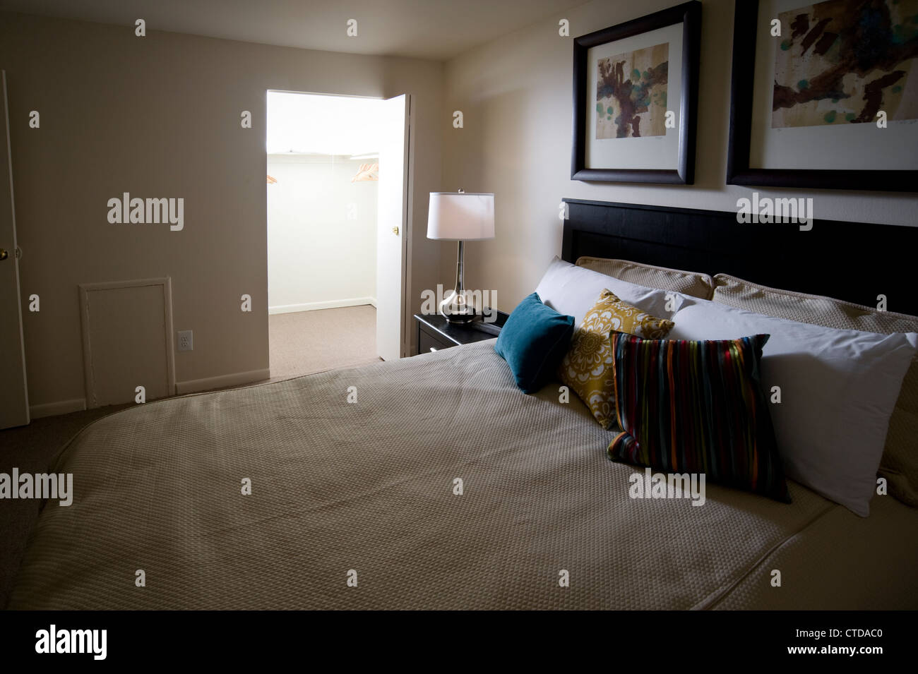 Bed In Bedroom With Bright Light Coming From Closet At Night - Stock Image