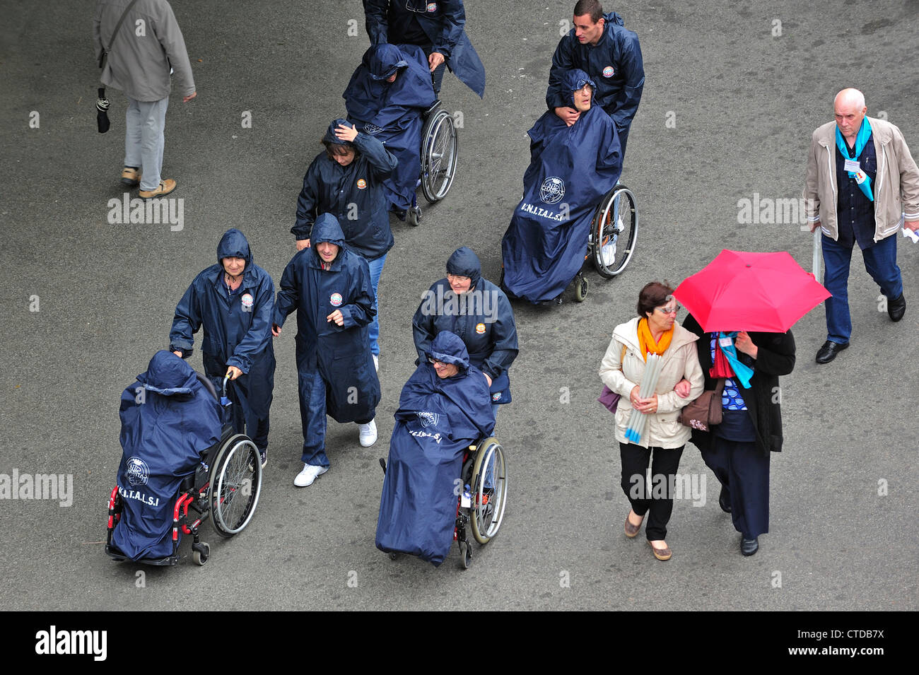 Disabled handicapped pilgrims in wheelchairs in the rain visiting Sanctuary of Our Lady of Lourdes, Pyrenees, France - Stock Image