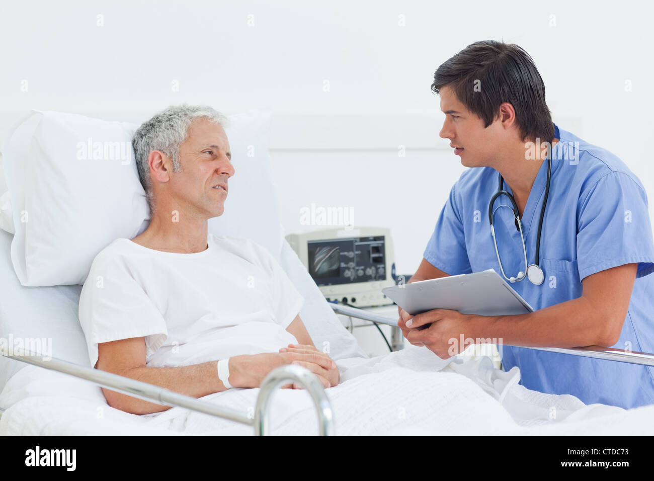 Nurse holding a clipboard as he talks to a patient - Stock Image
