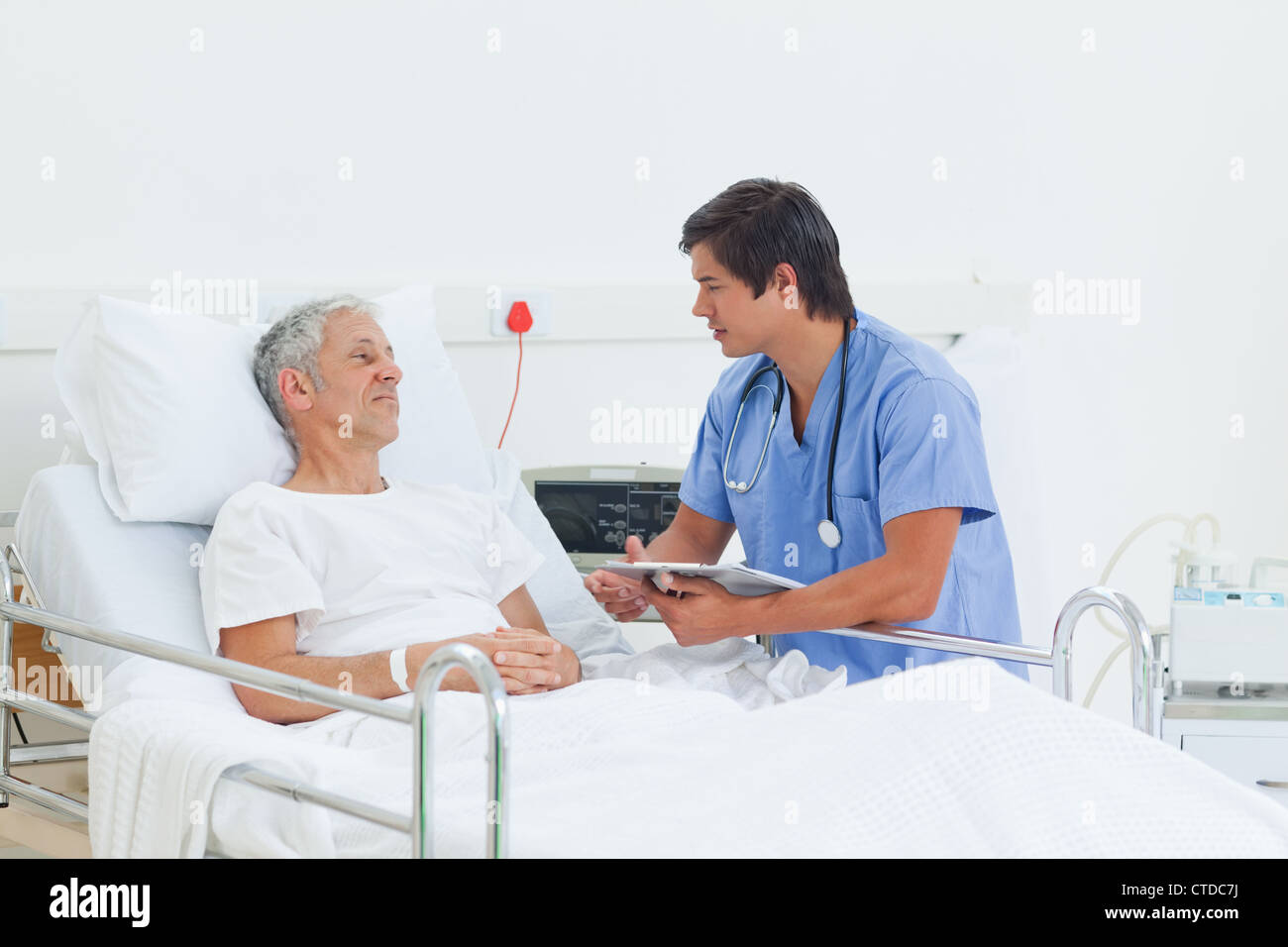 Nurse and a patient looking at each other with serious expressions - Stock Image
