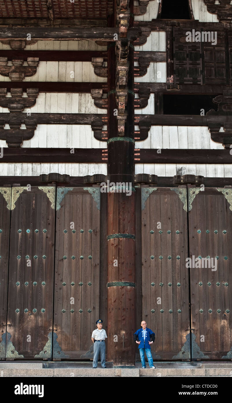 Nara, Japan. Two caretakers are dwarfed by scale of the Great Buddha Hall (Daibutsuden) at Todai-ji temple - Stock Image